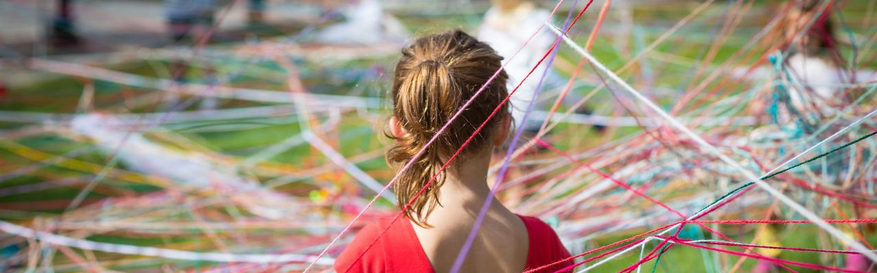 girl standing in a web of colored fiber