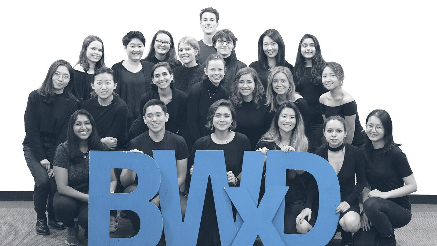Students at the Better World by Design conference pose with blue BWxD cutout letters