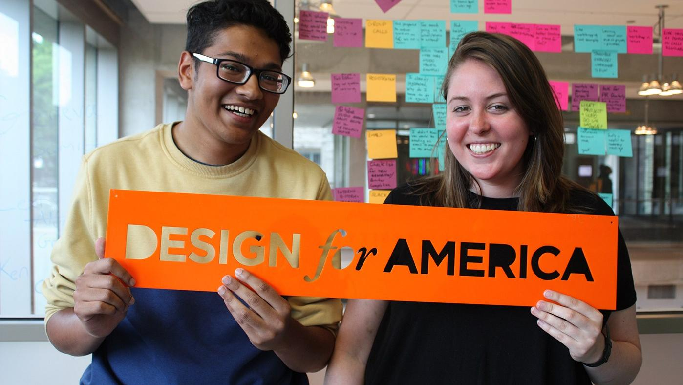 Two Design for America students hold an orange Design for America sign