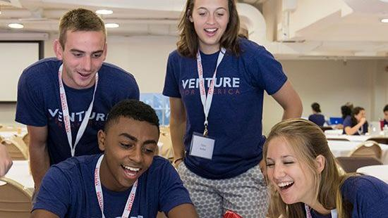 Four Venture for America students laugh as they look at a laptop