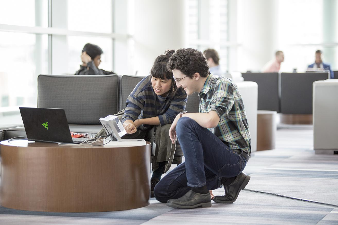 A student engages with an employer in the Student Waiting Area of the Design Portfolio Review.