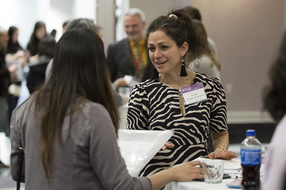 Employer networks with students at the Design Portfolio Review, Networking Reception.